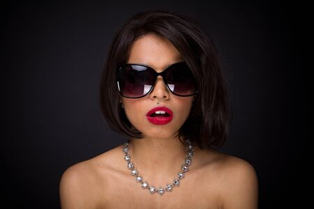 sexy brunette elegant woman expressed wearing neckles  and sunglasses photo