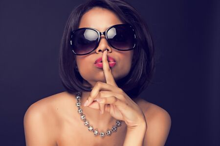 sexy brunette elegant woman expressing silence , using her finger  photo