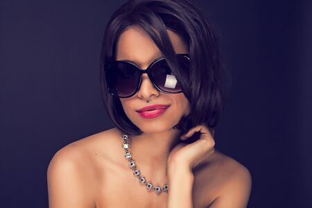 sexy brunette elegant woman wearing sunglasses and neckles  photo