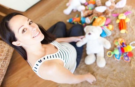Happy pregnant caucasian brunette  woman waiting arround toys for baby  photo