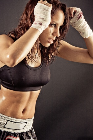 female boxer: toned female fitness boxer fighting with the shadow Stock Photo