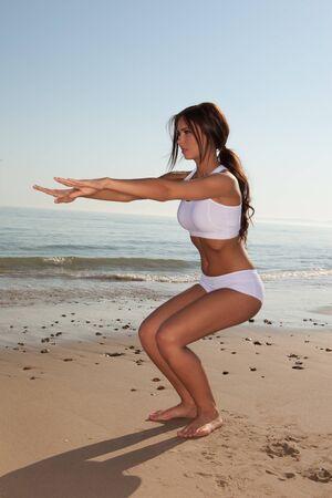 beach model: fitness brunette woman exercise on the beach