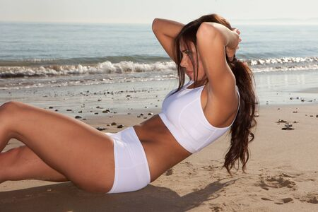 fitness brunette woman exercise on the beach Stock Photo - 9468869