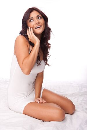 brunette happy woman speaking over the phone on white bed Stock Photo - 9501842