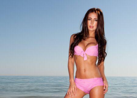 beach breast: sexy brunette woman in water wearing bikini