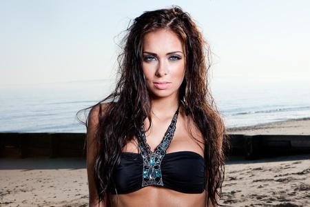 sexy brunette woman in water wearing bikini photo