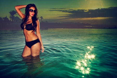 sexy brunette woman in water wearing bikini on sunset Stock Photo