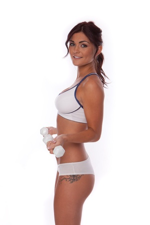 brunette fitness woman doing some exercises with dumbbells  photo