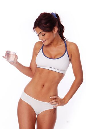 fitness woman on white background drinking water after workout photo