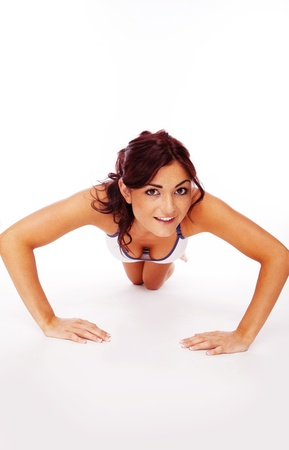 fitness brunette woman doing some push-ups on white photo