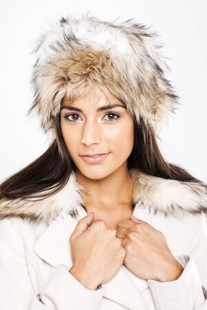 lapels: Beautiful Model In Coordinated Winter Fashion in a white coat with fur trim and matching fur hat. Stock Photo