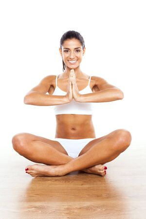 Beautiful Lady Practicing Yoga sitting cross legged with palms together.