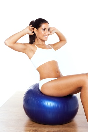 ball stretching: Sexy Woman Doing Aerobics stretching her raised arms while seated on a blue ball. Stock Photo