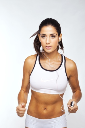 exertion: Beautiful Fit Girl Excercising To Music and holding a portable musical device while working out. Stock Photo