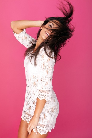 Playful young model in lacy garment having fun and flicking her hair against deep pink background. photo