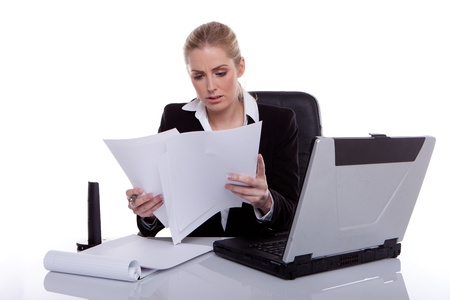 hardworking: Hardworking Businesswoman Consulting Notes while seated at her desk next to laptop. Stock Photo
