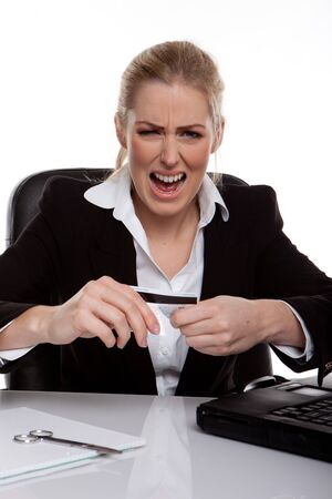 Businesswoman Throwing A Tantrum holding her credit card in her hands, seated at desk. photo