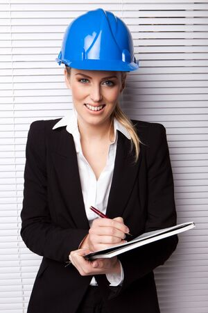 Smiling Businesswoman in Hard Hat facing camera holding a pen and notebook against white blind. photo