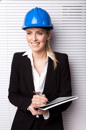 female construction worker: Confident Smiling Woman In Hard Hat holding pen and notebook, upper body