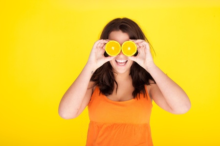 covering eyes: Fun Concept Model With Orange Slices For Eyes, laughing model holding oranges over eyes.
