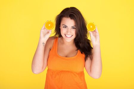 Cute Cheeky Woman Having Fun With Oranges, beautiful woman with cheeky smile holding up two orange slices Stock Photo - 12586023