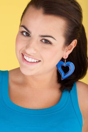 earings: Sexy Woman With Heart Earring beautiful smiling woman wearing turquoise with large matching turquoise heart earring. Stock Photo
