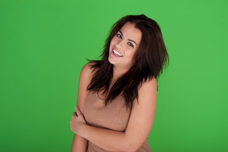 wild hair: Laughing Carefree Young Woman with long wild dark hair on green studio backdrop.