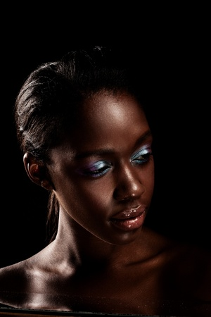 Glamorous African Beauty, beautiful African woman with blue eyeshadow on dark background.
