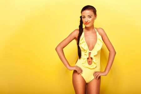 bathing costume: Sexy lady with long brunette hair modeling a bathing costume on yellow studio background with copyspace.