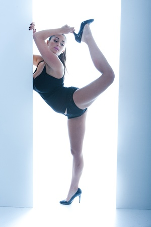 leotard: Athletic Woman Posing In Doorway, ballet pose on one leg, wearing high heels and a leotard