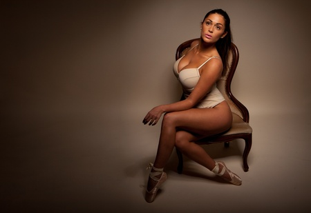 big breast: Dramatic Portrait Of Sexy Ballerina sitting sideways on a vintage chair facing towards camera and displaying large breasts and cleavage, dark background with ballerina highlighted, copyspace.