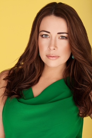 auburn hair: Beautiful Brunette In Green Dress. Beautiful brunette with subtle make-up gazing directly at the camera in an emerald green dress on yellow studio background.