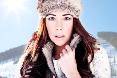 women subtle: Winter Woman On Ski Slope. Close-up headshot of a beautiful woman dressed in winter fur with a mountain ski slope background Stock Photo