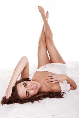 UÅ›miechniÄ™ty Uroda na łóżku, piÄ™kna mÅ'oda kobieta leży na plecach z gÅ'owÄ… nachylona do kamery i nogi skrzyżowane w powietrzu. Zdjęcie Seryjne