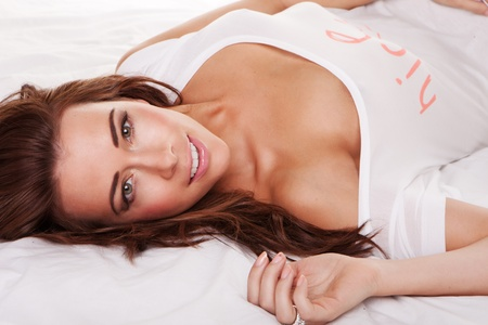skimpy: Beautiful smiling young woman lying on her back in a bed , close-up with head tilted to camera.