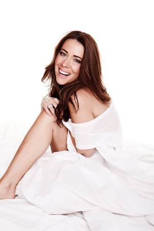 skimpy: Laughing Happy Young Woman sitting on a bed swathed in white bedclothes, studio on white
