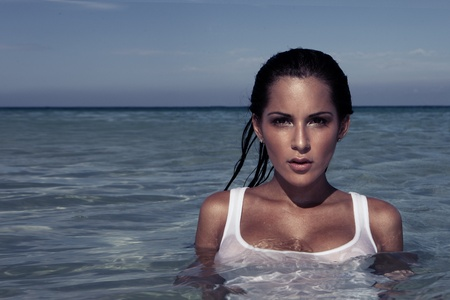 sultry: Beautiful brunette woman with wet hair standing chest high in the ocean , copyspace