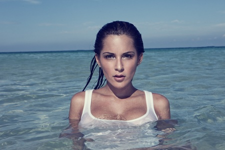beautiful brunette: Beautiful brunette woman with an enigmatic expression standing chest deep in the sea, copyspace