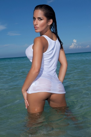 Provocative And Sensual Woman standing in the ocean wearing a wet shirt clinging to her curvy bum and breasts Foto de archivo