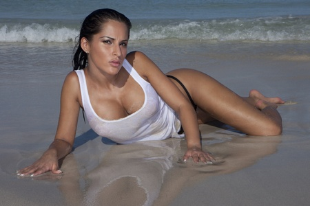wet breast: Provocative Sexy Woman On Wet Beach Sand lying facing towards the camera showing her cleavage with a small incoming wave behind. Stock Photo