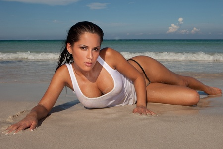 nude wet: Seductive model lying looking at the camera on a sandy beach and showing her cleavage, ocean and surf behind
