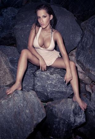 beaux seins: Belle Sexy Model Sur Rocks portant un costume de bain en montrant ses gros seins et les jambes écartées.