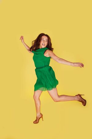 Happy woman in green dress leaping for joy on yellow studio background photo