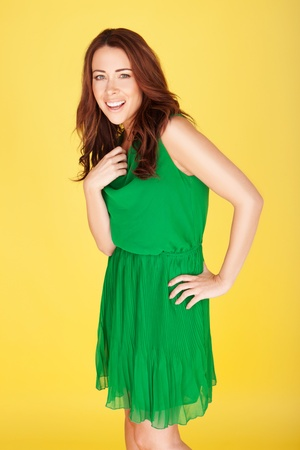 Laughing Young Woman wearing a green dress, three quarter on yellow studio background photo
