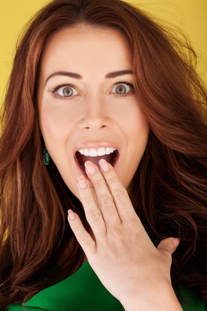 Beautiful redhead woman with her hand to her mouth and wide eyes in a shocked expression photo
