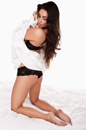 mujer arrodillada: Sensual morena en ropa interior negro y con una sábana blanca colgada en su rodillas en una cama mirando hacia atrás por encima del hombro Foto de archivo