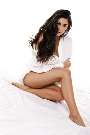 Sexy woman with long dishevelled brunette hair sitting on a bed wrapped in a small white sheet photo