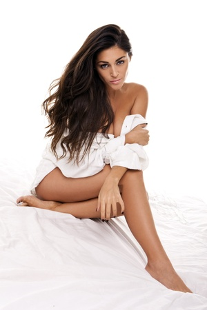 Beautiful Woman Posing On A Bed, seated on white bedclothes with a small white garment wrapped around her middle, studio on white. photo