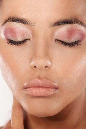 A clsoeup beaty shot af a young womans face wearing subtle magenta eyeshadow, eyes, closed. photo