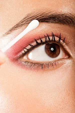 Applying Eye Makeup Eye Open. Woman with brown eyes using a cotton bud to blend her eye makeup, closeup on eye. photo